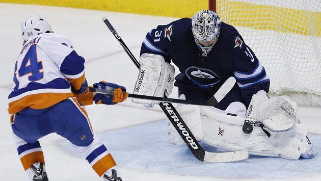 Ondřej Pavelec v brance Winnipegu zastavuje útok Michaila Grabovského z New Yorku Islanders.