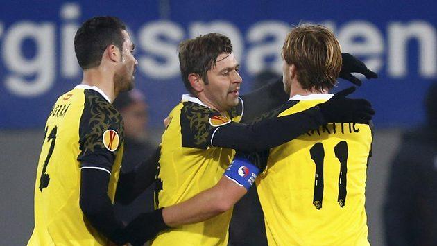 Fotbalisté Sevilly Vicente Iborra (vlevo), Raul Rusescu (uprostřed) a Ivan Rakitic se radují z branky proti Freiburgu.