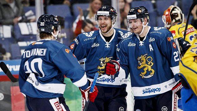 Finští hokejista (zleva) Eeli Tolvanen, Jukka Peltola a Petri Kontiola se radují z gólu proti Švédsku na turnaji Karjala.