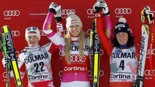 Američanka Lindsey Vonnová (uprostřed) po výhře v nedělním sjezdu v Cortině, vlevo Rakušanka Elisabeth Görglová a na třetím stupínku Daniela Merighettiová, která si o den později při super-G zlomila čelist nárazem do branky.