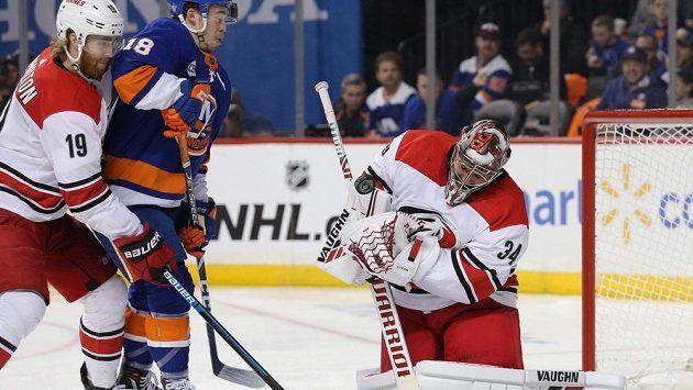Petr Mrázek v brance Caroliny zasahuje před útočníkem Anthonym Beauvillierem z New York Islanders.