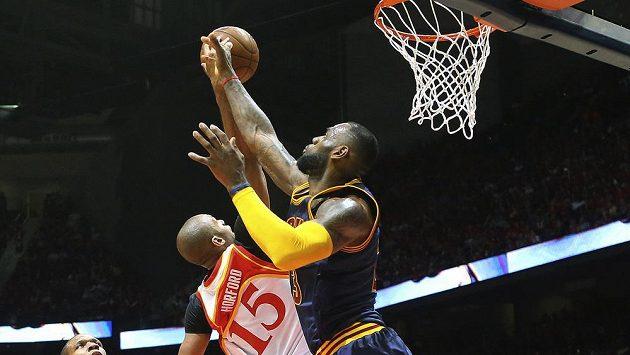 LeBron James z Clevelandu se probíjí ke koši. Blokovat se ho snaží atlantský Al Horford.