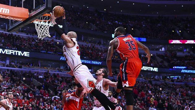Taj Gibson z Chicaga zavěšuje v zápase s Washingtonem. Vpravo přihlíží nene Hilario z týmu Wizards.