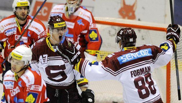 Sparťanští útočníci Jan Buchtele (č. 47) a Miroslav Forman se radují z gólu na ledě Pardubic.