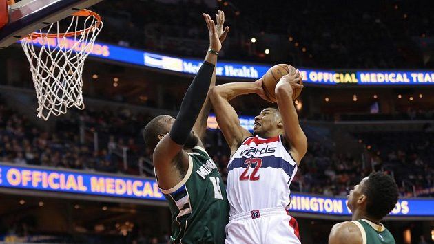 Basketbalista Washingtonu Otto Porter Jr. (č. 22) a Greg Monroe z Milwaukee (vlevo) v zápase NBA.