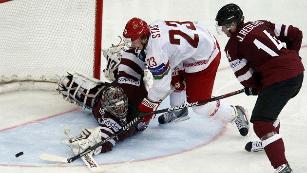 Lotyšský brankář Edgars Masalskis zasahuje za asistence Jekabse Redlihse před běloruským útočníkem Andrejem Stasem.