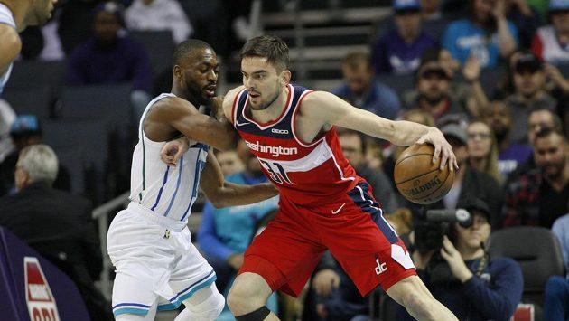 Tomáš Satoranský z Washingtonu se snaží prosadit proti hlavní hvězdě Charlotte Kemba Walkerovi v zápase NBA.