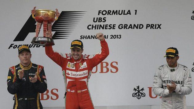 Fernando Alonso se raduje s pohárem pro vítěze GP v Šanghaji. Vlevo druhý v cíli Kimi Räikkönen, zcela vpravo třetí Lewis Hamilton.