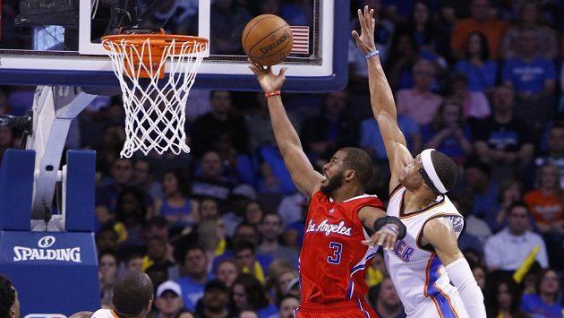 Basketbalista Los Angeles Clippers Chris Paul (3) zakončuje přes bránícího Russella Westbrooka z Oklahomy.