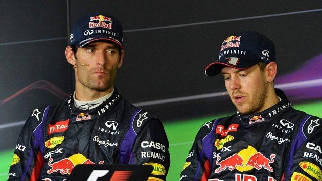 Mark Webber (vlevo) propichuje očima svého stájového kolegu ze stáje Red Bull Sebastiana Vettela na tiskové konferenci po Velké ceně Malajsie.