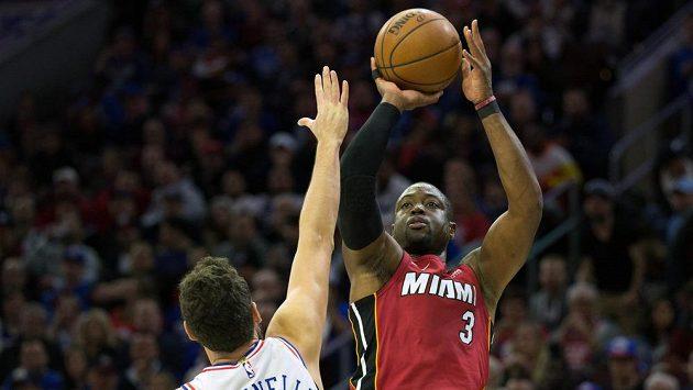 Dwyane Wade (3) z Miami střílí přes hráče Philadelphie Marka Belinelliho (18).