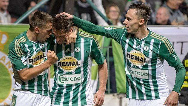 Fotbalisté Bohemians (zleva): Milan Kočič, Jevgenij Kabajev a Siim Luts oslavují gól proti Baníku.