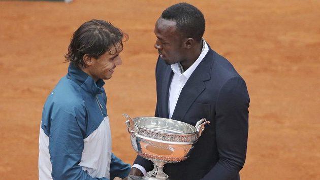 Rafael Nadal (vlevo) přebírá trofej pro vítěze Roland Garros od Usaina Bolta.