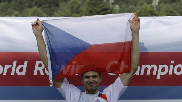 Ondřej Synek se raduje s českou vlajkou nad hlavou.