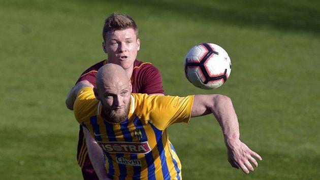 Tomáš Smola z Opavy (vepředu) v souboji s Michalem Bezpalcem v dresu Dukly v zápase 26. kola Fortuna ligy.