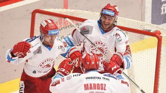 Zleva Tomáš Linhart, Rostislav Marosz a Jakub Petružálek z Třince se radují z vítězné branky v prodloužení proti Brnu.