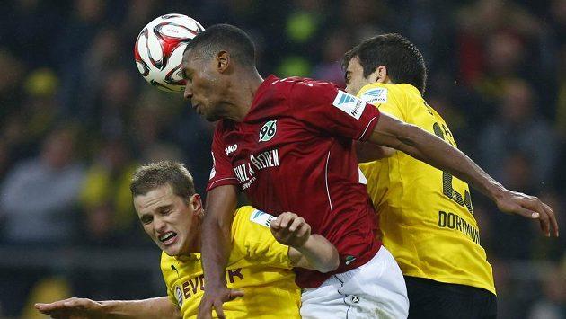 Fotbalisté Borussie Dortmund Sven Bender (vlevo) a Sokratis (vpravo) bojují o míč s Marcelem-Guedesem z Hannoveru.