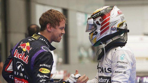 Úřadující mistr světa Vettel (vlevo) gratuluje Hamiltonovi k vítězství v malajsijské kvalifikaci.