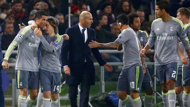 Cristiano Ronaldo (vlevo) z Realu Madrid jásá se spoluhráči a trenérem Zinedinem Zidanem při utkání s AS Řím.