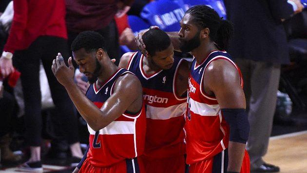 Basketbalisté Washingtonu John Wall (vlevo), Trevor Ariza (uprostřed) a Nene Hilario se radují z postupu přes Chicago.
