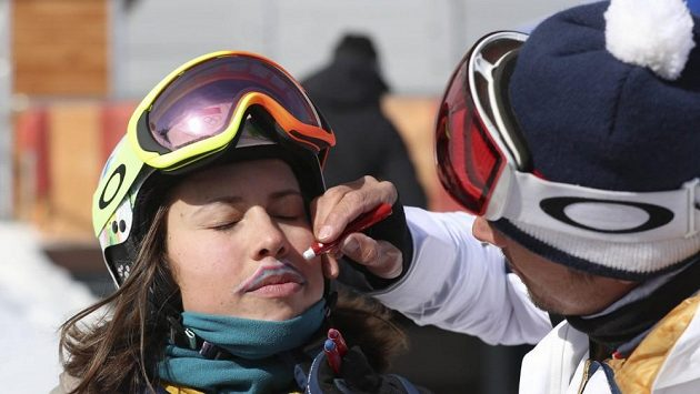 """Trenér Jakub Flejšar pomohl před startem závodu Evě Samkové s tvorbou jejího kníru. Když pak získala bronz, v novinářské mixzóně před ní poklekl a symbolicky políbil její """"bronzové"""" nohy, a pak se jí zakousl do stehna."""