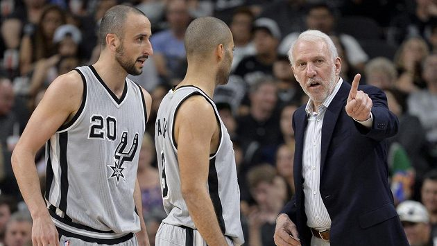 Basketbalisté San Antonia Manu Ginobili (vlevo) a Tony Parker naslouchají pokynům trenéra Gregga Popoviche.