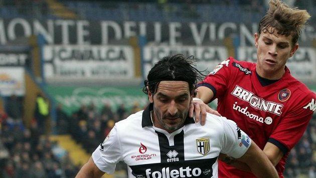 Alessandro Lucarelli z Parmy (vlevo) si kryje míč před Samuelem Longem z Cagliari.