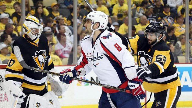 Obránce Pittsburghu Kris Letang (vpravo) atakuje Alexe Ovečkina z Washingtonu. Vlevo brankář Tučňáků Matt Murray.
