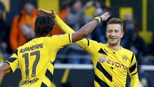Dortmundští Pierre-Emerick Aubameyang (vlevo)a Marco Reus oslavují jednu z branek proti Schalke.