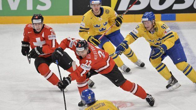 Švýcarského hokejistu Nina Niederreitera (uprostřed) stíhá Švéd Gabriel Landeskog (vpravo) v utkání MS skupiny A.