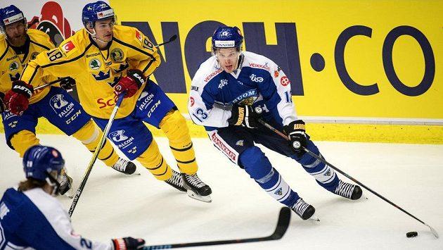 Finský útočník Mika Niemi (vpravo) se snaží prosadit přes švédskou obranu.