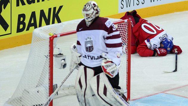 Zraněný Jakub Klepiš v první třetině za lotyšskou brankou, vpředu brankář Edgars Masalskis.