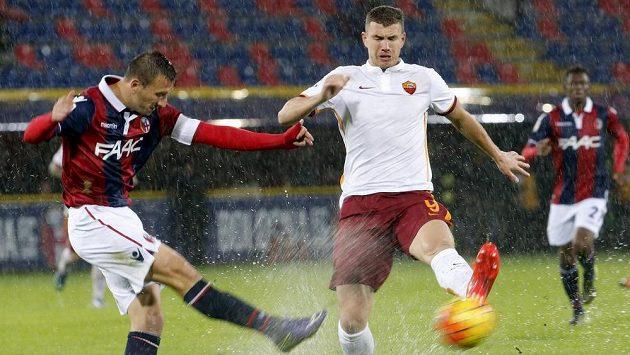 Daniele Gastaldello z Boloni odkopává míč před Edinem Džekem z AS Řím.