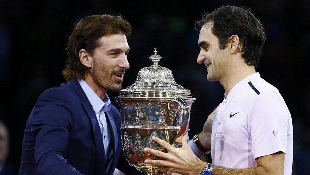 Bývalý cyklista Fabian Cancellara (vlevo) předává na turnaji v basileji trofej Rogeru Federerovi.