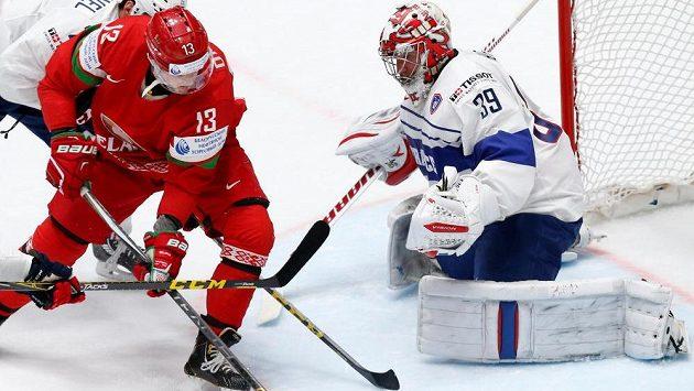 Běloruský hokejista Sergej Drozd před francouzským brankářem Cristobalem Huetem.
