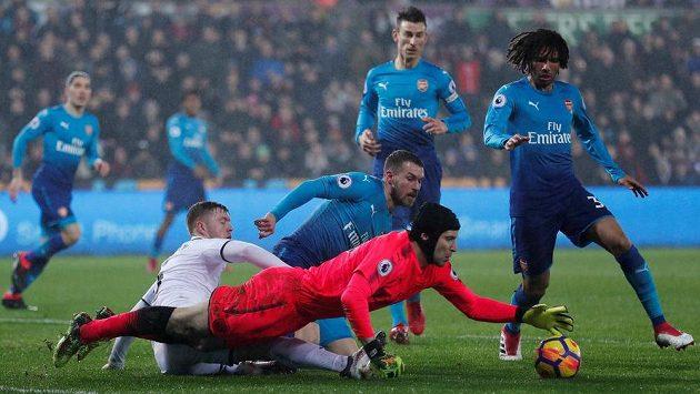 Petr Čech v brance Arsenalu zasahuje v ligovém utkání oproti Swansea.