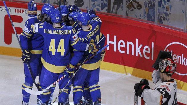 Hokejisté Švédska oslavují branku proti Německu