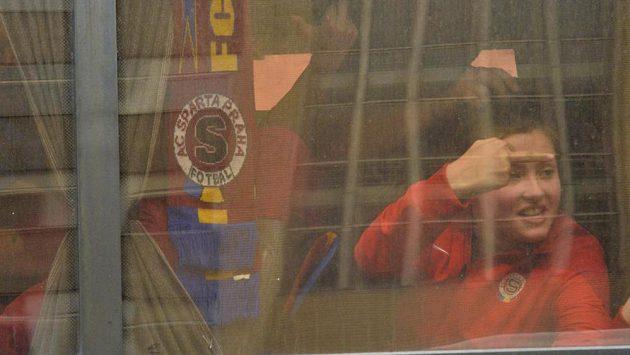Příznivec Sparty gestikuluje z autobusu na fanoušky Slavie.