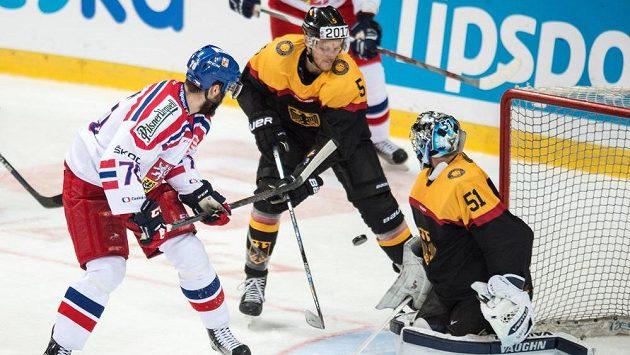 Český obránce Bohumil Jank (vlevo na archivním snímku) se snaží tečovat puk před německým brankářem Timem Pielmeierem. Uprostřed německý obránce Benedikt Brückner.