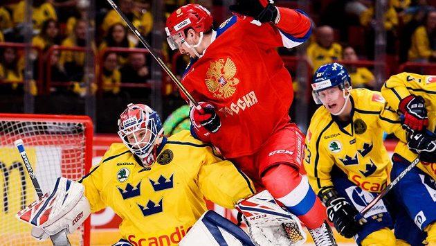 Ruský hokejista Artur Kayumov a švédský brankář Lars Johansson v souboji.