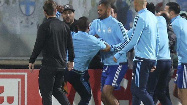 Patrice Evra z Marseille (třetí zleva) kope do fanouška.