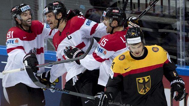 Thomas Raffl z Rakouska (druhý zleva) se raduje z gólu. Na snímku jsou jeho spoluhráči zleva Dominique Heinrich a Manuel Latusa a Benedikt Kohl z Německa.