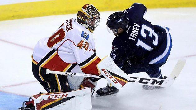 Brankáře Calgary Davida Ritticha (40) se snaží překonat Brandon Tanev z Winnipegu.