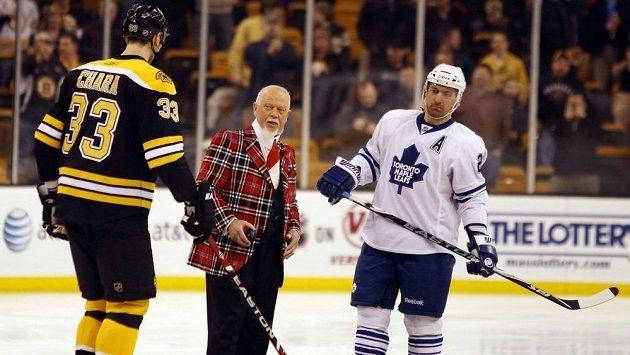 Don Cherry (uprostřed) se chystá vhodit puk mezi Francoise Beauchemina (v bílém) z Toronta a bostonského beka Zdena Cháru.