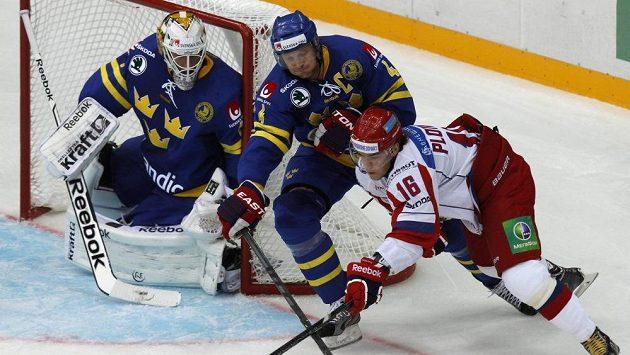 Ruský hokejista Sergej Plotnikov (vpravo) se snaží překonat švédského gólmana Henrika Karlssona (vlevo), v čemž mu brání Staffan Kronwall.