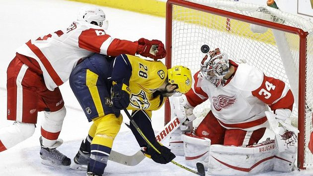 Český gólman Petr Mrázek (34) z Detroitu Red Wings za pomoci zadáka Dannyho DeKeysera (65) likviduje pokus Paula Gaustada (28) z Nashvillu.