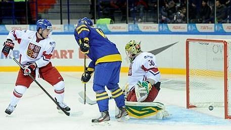 Švédský hokejista Elias Lindholm (v modrém) překonává českého brankáře Matěje Machovského na MS hráčů do 20 let.