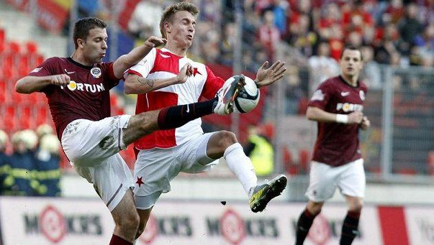 Sparťan Hušbauer ukopává míč před slávistou Petrákem v pražském derby.