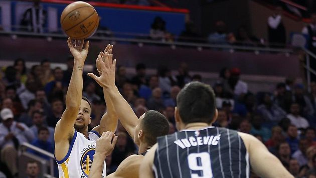 Stephen Curry z Golden State Warriors (vlevo) střílí za tři body v zápase s Orlandem.