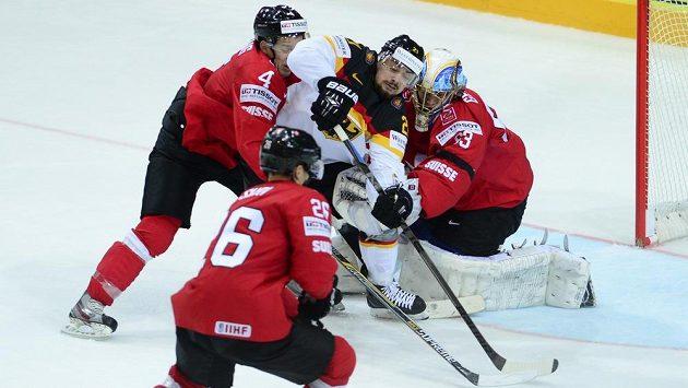 Švýcarští hokejisté Patrick Geering a Reto Suri (zleva) v klinči s Němcem Nicolasem Krammerer před švýcarskou bránou střeženou Leonardem Genonim.